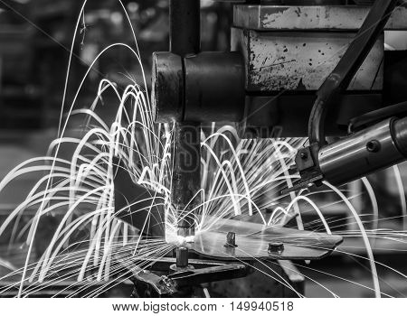 Industrial, automotive spot welding in automotive part in factory. black white