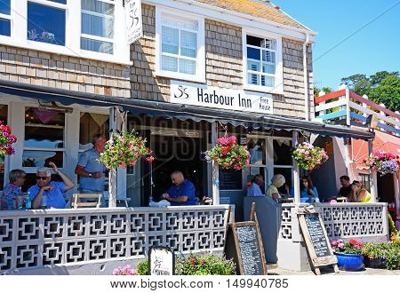 LYME REGIS, UNITED KINGDOM - JULY 18, 2016 - Tourists relaxing on the terrace of the Harbour Inn pub along the promenade Lyme Regis Dorset England UK Western Europe, July 18, 2016.