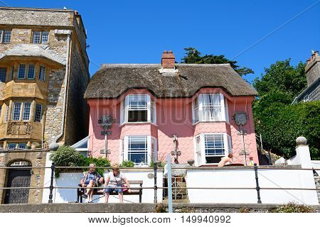 LYME REGIS, UNITED KINGDOM - JULY 18, 2016 - View of the pink painted thatched Library cottage along Marina Parade Lyme Regis Dorset England UK Western Europe, July 18, 2016.