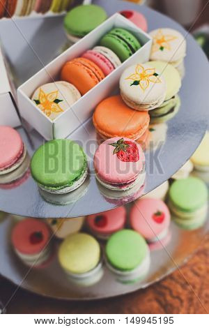 Beautiful Macarons choice. Plenty of colorful french cookies, meringue based confectionery desserts on counter bar for sale. Pastel colors, packed in boxes and stacks closeup, vertical image