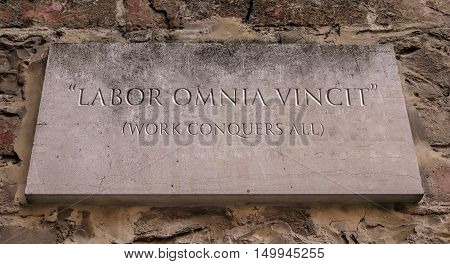 Labor omnia vincit. A Latin phrase meaning Work conquers all. Engraved text.