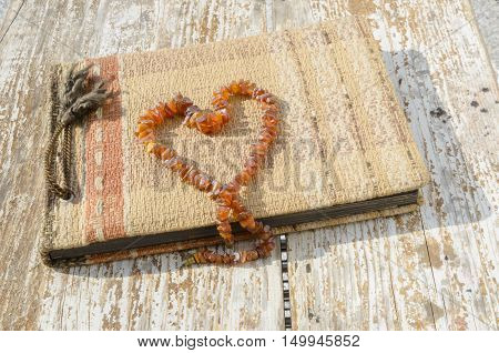 Old photo album with heart created from amber necklace