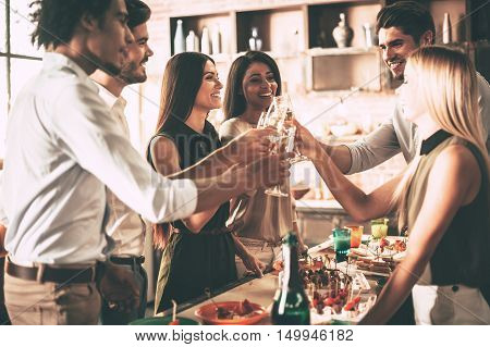Cheers to friends! Group of cheerful young people cheering with champagne flutes and looking happy while having party on the kitchen
