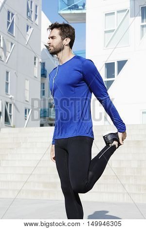 Athletic guy stretching in sportswear in town