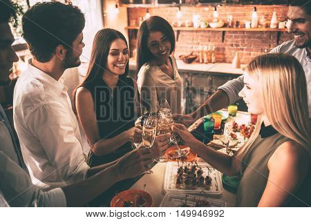 To the best friends ever! Top view of cheerful young people cheering with champagne flutes and looking happy while having party on the kitchen