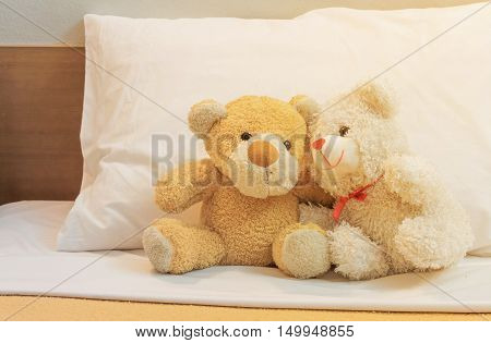 Teddy bears fall in love on a bed of white vintage filters.