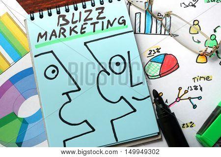 Buzz marketing written on a blue paper.