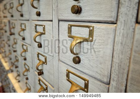 Photo closeup of old furniture wooden. vintage metal handles furniture background. Drawers with blank tags in vintage furniture module