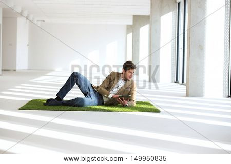 Full length of young businessman using tablet computer while reclining on turf in office