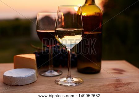 Low Key Image, Two Glasses Of Wine With Cheese On Table, Toned At Sunset.