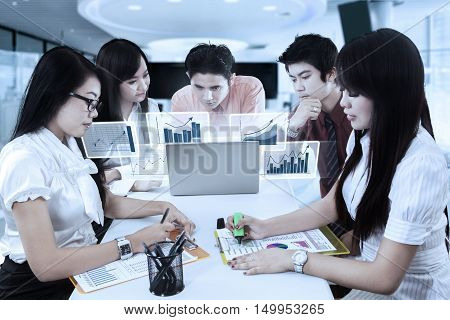 Picture of business team working in the office with virtual financial chart on the laptop