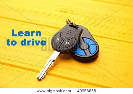Learn to drive. Car key on yellow table