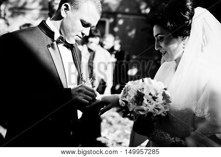 Groom Puts A Wedding Ring On The Finger Of Bride