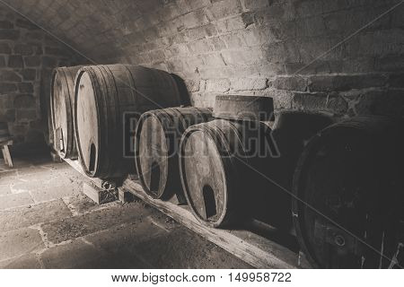 Vintage image with old wooden wine barrels - Retro style image with the interior of an old wine cellar with stone walls and obsolete wooden barrels.