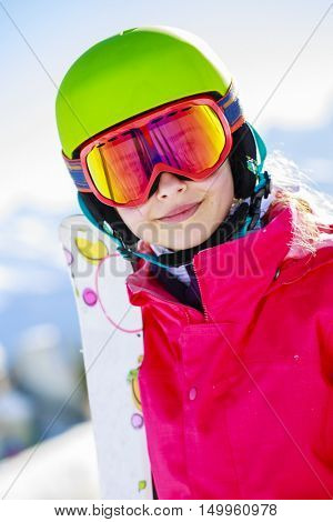 Girl standing portrait on the fresh powder snow at sunny day in mountains. Swiss Alps.