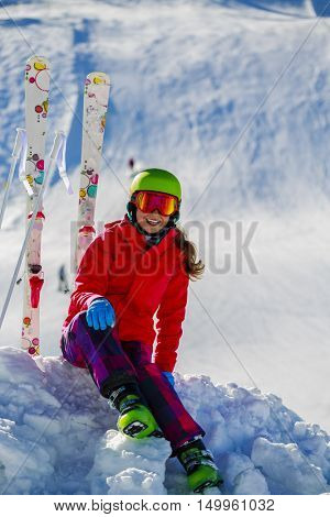 Girl sitting on the fresh powder snow at sunny day in mountains. Swiss Alps.