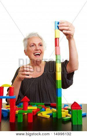 Senior Woman Building Block Tower