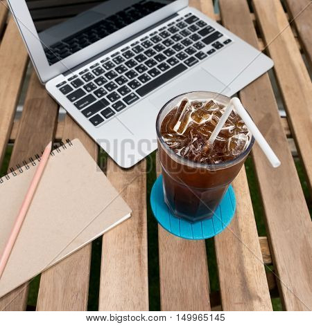 cup of coffee with Laptop (notebook) and notepad with pen on old wooden table.