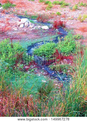Raw sewage flowing in open countryside next to river in Alora Andalucia