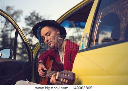 Woman guitarist playing music in car outdoors