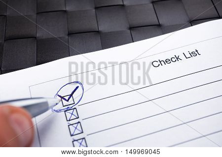 Checklist with hand doing tick mark with a pen on checkered black background.