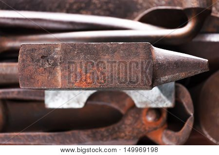 Old rusty rugged anvil on other blacksmith tools. Top view.