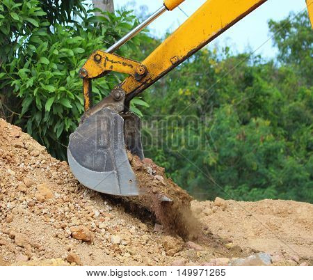 excavation power bucket scooping up dirt onto a pile near Songkhla, Thailand