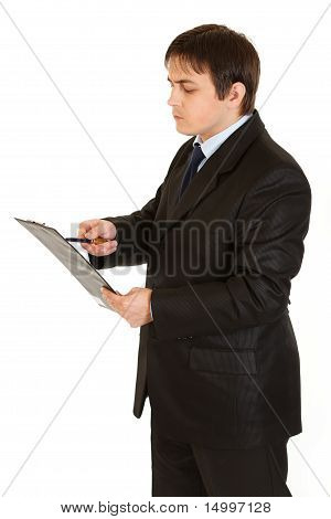 Concentrated businessman holding clipboard and checking notes isolated on white