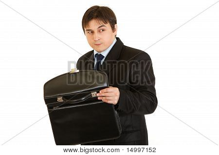 Suspicious businessman holding open briefcase in hands isolated on white