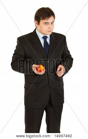 Thoughtful modern businessman holding apple in hand isolated on white