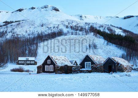 Icelandic turf houses at dawn in winter,  behind it the mountain range Eyjafjoll, Skogar,  Iceland.