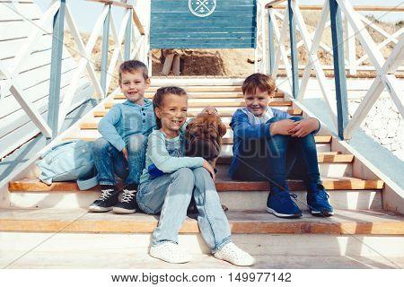 Group of fashion children wearing denim clothing with dog having fun on the sea shore. Autumn casual outfit in blue and navy color. 7-8 years old models.