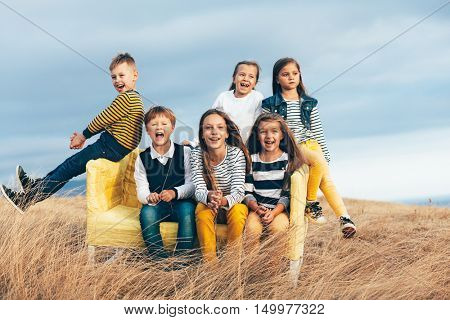 Group of fashion children wearing same style clothing resting on a sofa in the autumn field. Fall casual outfit in navy and yellow colors. 7-8, 8-9, 9-10 years old models sitting on a coach outdoor.