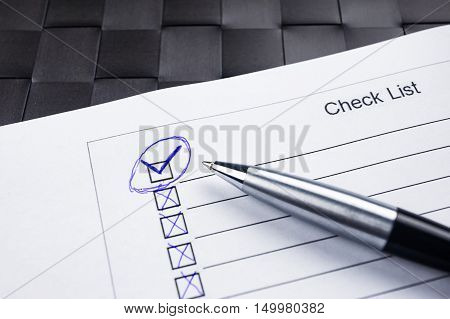 Checklist with a pen with check mark tick on black background.