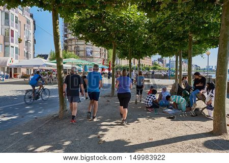 DUESSELDORF, GERMANY - AUGUST 17, 2016: Unidentified joggers pass a group of unidentified people who take a rest around a bench at Rhine promenade