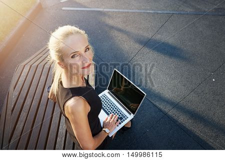 Businesswoman Sitting On Bench Working Outside