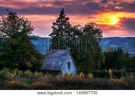 Small hillside cottage at neautiful pieceful sunset