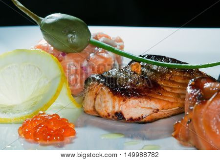 macro delicious dish of fried fish caviar lemon decorated with cherry tomatoes and capers studio on dark background