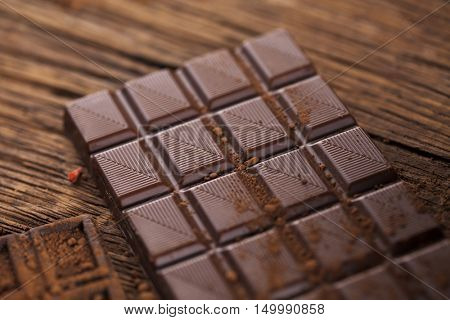 Chocolate bar, candy sweet, cacao beans and powder on wooden background