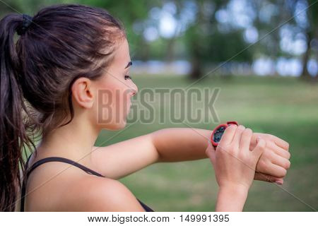 Ftitness Girl Checks Watch Tracker On Her Wrist During Run