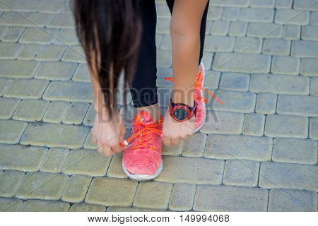 Young Fitness Girl Ties Up Shoestrings Preparing For Working-out