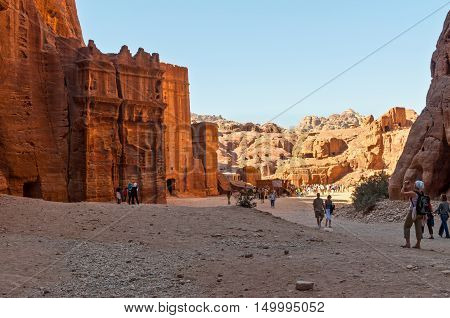 Petra Jordan - November 20 2010: Tourists walk in one of the Seven Wonders of the World - Red city of Petra in Jordan. Petra has been a UNESCO World Heritage Site since 1985
