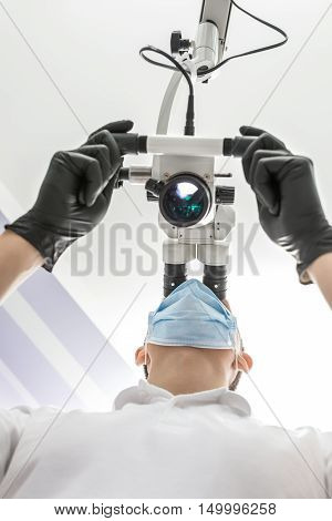 Rational doctor is using the dental microscope in the clinic. He is wearing a white uniform, black gloves and a blue medical mask. The microscope is glowing. View from the bottom. Vertical.