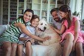 Family sitting on sofa with pet dog in living room at home poster