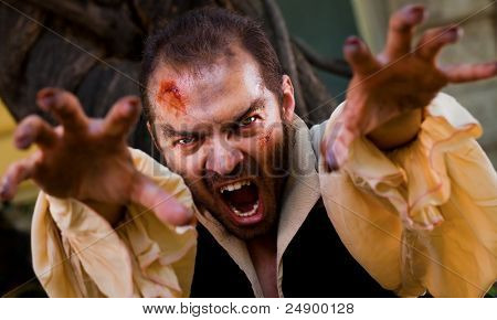 Evil male vampire reaching hands to the camera and roaring