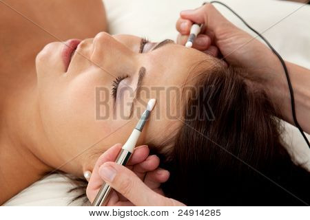 Attractive female patient receiving electro acupuncture on face as part of a anti-aging beauty treatment