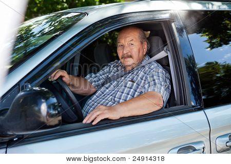 Portrait of an elderly man driving a car