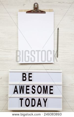 poster of Work Space With Noticepad, Pencil And 'be Awesome Today' Word On Lightbox Over White Wooden Backgrou