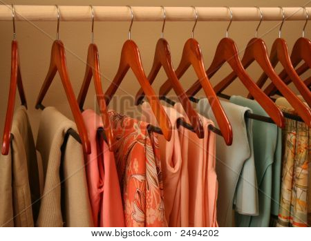 Spring Colored Sweaters On Wooden Hangers