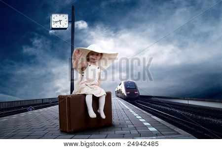 Little girl sitting on vintage baggage on the train platform of railway station